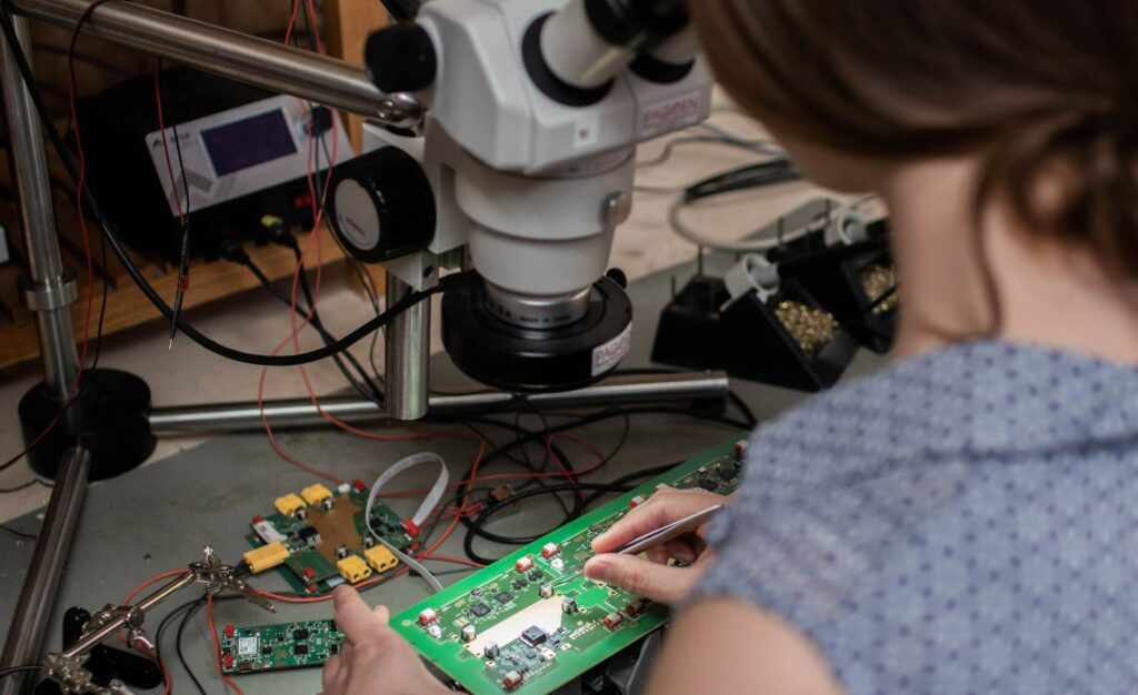 Employee soldering a component with a microscope